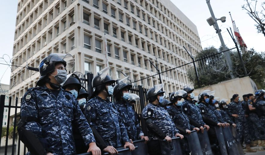 FILE - In this April 23, 2020 file photo, Lebanese riot police stand guard in front the central bank building, where the anti-government protesters protest against the Lebanese central bank's governor Riad Salameh and the deepening financial crisis, in Beirut, Lebanon. A New-York-based company that was contracted by Lebanon's government to conduct a forensic audit of the country's central bank has decided to pull out of the deal because it was not able to acquire needed information and documents, Lebanese outgoing finance minister said Friday, Nov. 20, 2020. (AP Photo/Hussein Malla, File)