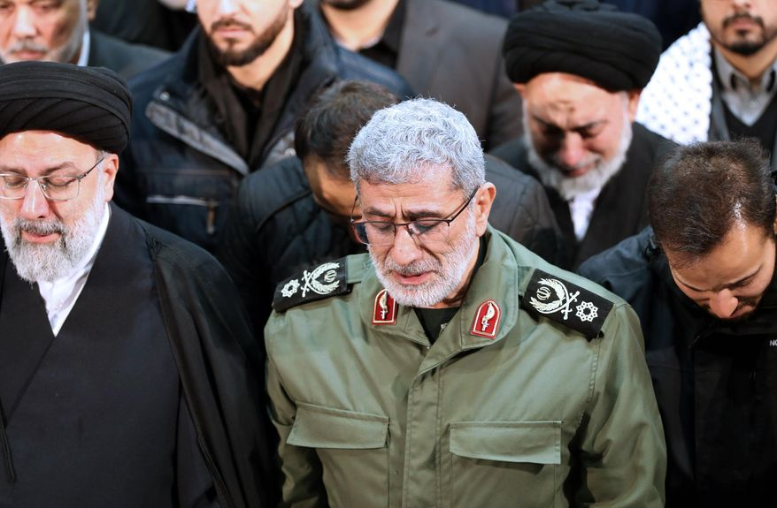 FILE - In this photo released by the official website of the Office of the Iranian Supreme Leader, Gen. Esmail Ghaani, newly appointed commander of Iran's Revolutionary Guards Quds Force, weeps while praying over the coffin of the force's previous head Gen. Qassem Soleimani at the Tehran University Campus in Tehran, Iran, Monday, Jan. 6, 2020.  On Friday, Nov. 20, two Iraqi officials say Iran has instructed allies in the Middle East to be on high alert and avoid provoking tensions with the U.S. that could give an outgoing Trump Administration cause to launch attacks in his final weeks in office.   (Office of the Iranian Supreme Leader via AP)
