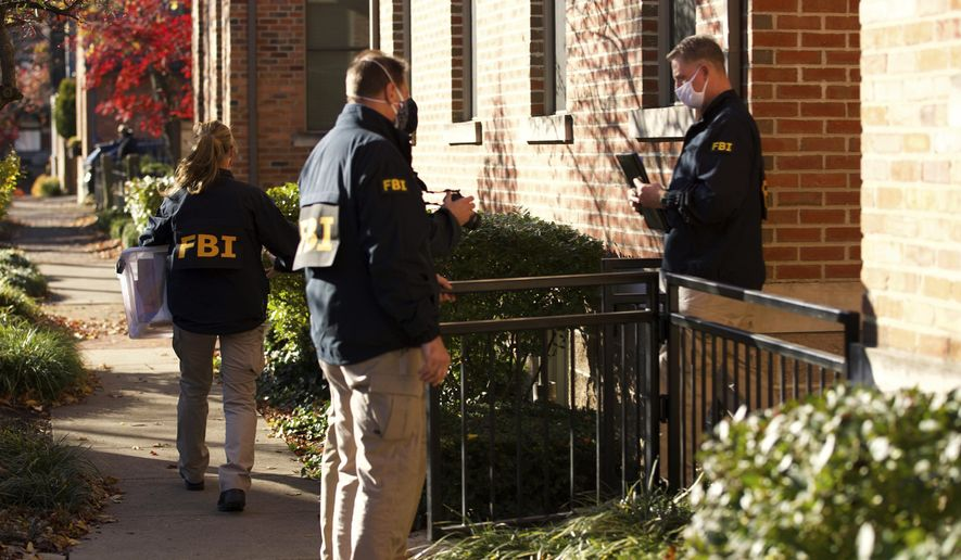FILE-This Monday, Nov. 16, 2020 file photo shows FBI agents removing items from the German Village home of Public Utilities Commission of Ohio Chairman Sam Randazzo in Columbus, Ohio.   Just days after FBI agents searched Randazzo's upscale townhome in Columbus, FirstEnergy revealed Thursday that the firm of an Ohio regulator fitting Randazzo's description received a $4 million payment for purported consulting work just before taking his government position early last year.    (Adam Cairns/The Columbus Dispatch via AP)