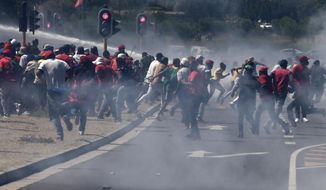 Members of the Economic Freedom Fighters (EFF) flee from teargas, stun grenades and water canons fired by police during a protest near the Brackenfell High school in Cape Town, South Africa, Friday, Nov. 20, 2020. The EFF party organized protests at the school in response to a students' prom they claim only white kids were invited to. (AP Photo/Nardus Engelbrecht)