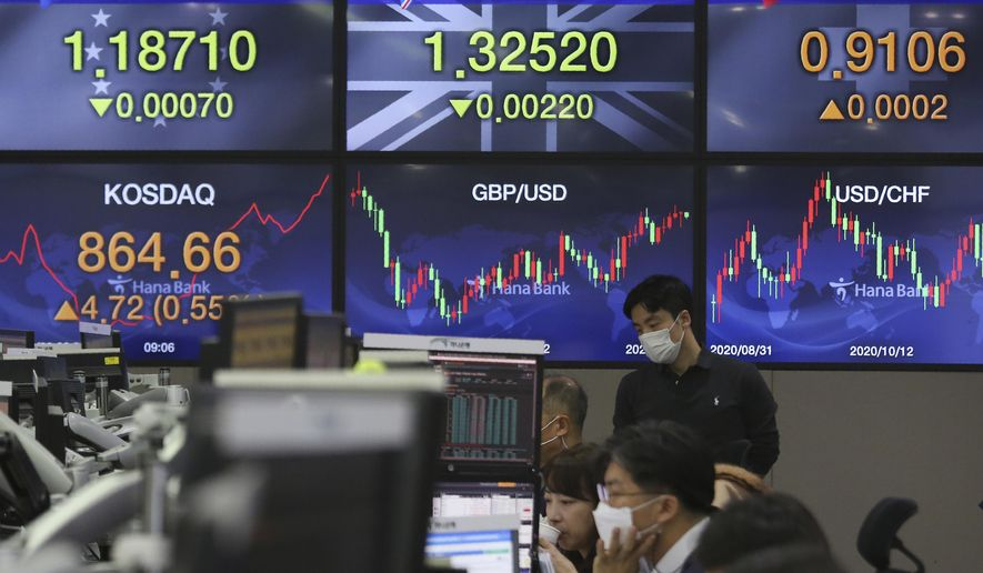 A currency trader watches monitors at the foreign exchange dealing room of the KEB Hana Bank headquarters in Seoul, South Korea, Friday, Nov. 20, 2020. Asian shares mostly rose in muted trading Friday after Wall Street eked out modest gains amid a tug of war between worries about the worsening pandemic in the present and optimism that a vaccine will rescue the economy in the future. (AP Photo/Ahn Young-joon)