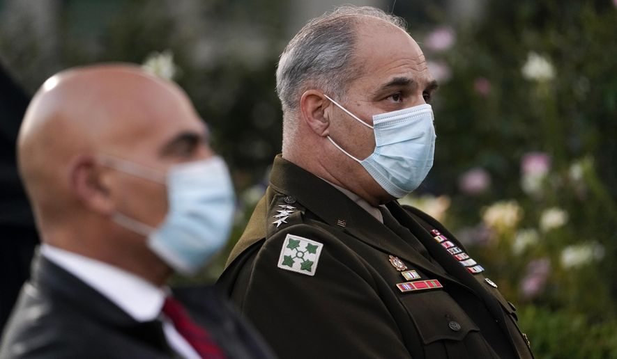 In this file photo, Army Gen. Gustave Perna, who is leading Operation Warp Speed,right, and Dr. Moncef Slaoui, chief adviser to Operation Warp Speed, listen during at an event in the Rose Garden of the White House, Friday, Nov. 13, 2020, in Washington. (AP Photo/Evan Vucci)  **FILE**