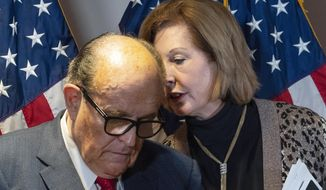Former Mayor of New York Rudy Giuliani, left, President Trump's personal lawyer, listens to Sidney Powell during a news conference at the Republican National Committee headquarters, Thursday, Nov. 19, 2020, in Washington. (AP Photo/Jacquelyn Martin)