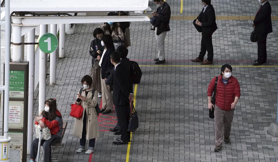 Commuters wearing face masks to help curb the spread of the coronavirus maintain social distancing to wait for a bus during a rush hour in Tokyo Friday, Nov. 20, 2020. (AP Photo/Eugene Hoshiko)