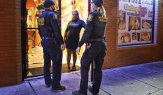 FILE - In this Nov. 12, 2020, file photo, police officers remind a woman in the doorway of a Newark, N.J., restaurant of the new curfew and dining regulations in an area where coronavirus cases have recently spiked. During a Nov. 19 radio interview, Newark Mayor Ras Baraka said that he'll ask residents of New Jersey's largest city to stay home for 10 days starting next week, right before Thanksgiving, in response to a rising number of COVID-19 cases. (AP Photo/Seth Wenig, File)