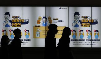 """People wearing face masks walk past a screen showing the precautions against the coronavirus in Seoul, South Korea, Friday, Nov. 20, 2020. The screen reads: """"Don't wear such masks like below images."""" (AP Photo/Lee Jin-man)"""