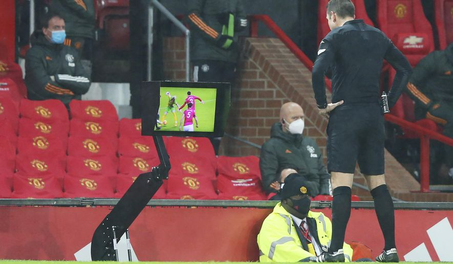 Referee David Coote checks the VAR screen during the English Premier League soccer match between Manchester United and West Bromwich Albion at the Old Trafford stadium in Manchester, England, Saturday, Nov. 21, 2020. (Alex Livesey/Pool via AP)