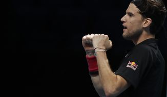 Dominic Thiem of Austria celebrates after winning his semifinal match against Novak Djokovic of Serbia at the ATP World Finals tennis tournament at the O2 arena in London, Saturday, Nov. 21, 2020. (AP Photo/Frank Augstein)