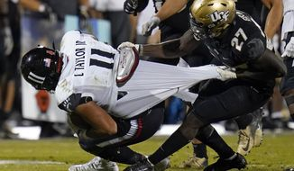 Cincinnati tight end Leonard Taylor (11) is stopped by Central Florida defensive back Richie Grant (27) during the second half of an NCAA college football game, Saturday, Nov. 21, 2020, in Orlando, Fla. (AP Photo/John Raoux)