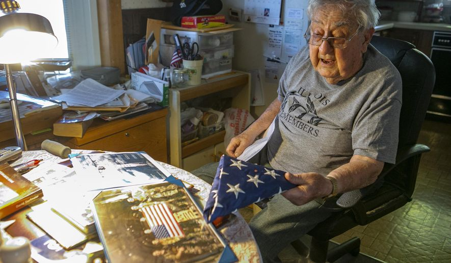 Robert Teichgraeber, 100, talks about the many gifts and honors he has received for his service in World War II on Nov. 6, 2020 in Collinsville, Ill.. He holds a flag flown in his honor in combat over Afghanistan aboard a United States Air Force C-130J assigned to the 61st Expeditionary Airlift Squadron in July of 2000. He survived 421 days as a prisoner after his plane was shot down during a bombing run in WWII. (Derik Holtmann/Belleville News-Democrat via AP)