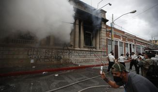 Clouds of smoke shoot out from the Congress building after protesters set it on fire, in Guatemala City, Saturday, Nov. 21, 2020. Hundreds of protesters were protesting in various parts of the country Saturday against Guatemalan President Alejandro Giammattei and members of Congress for the approval of the 2021 budget that reduced funds for education, health and the fight for human rights. (AP Photo/Moises Castillo)