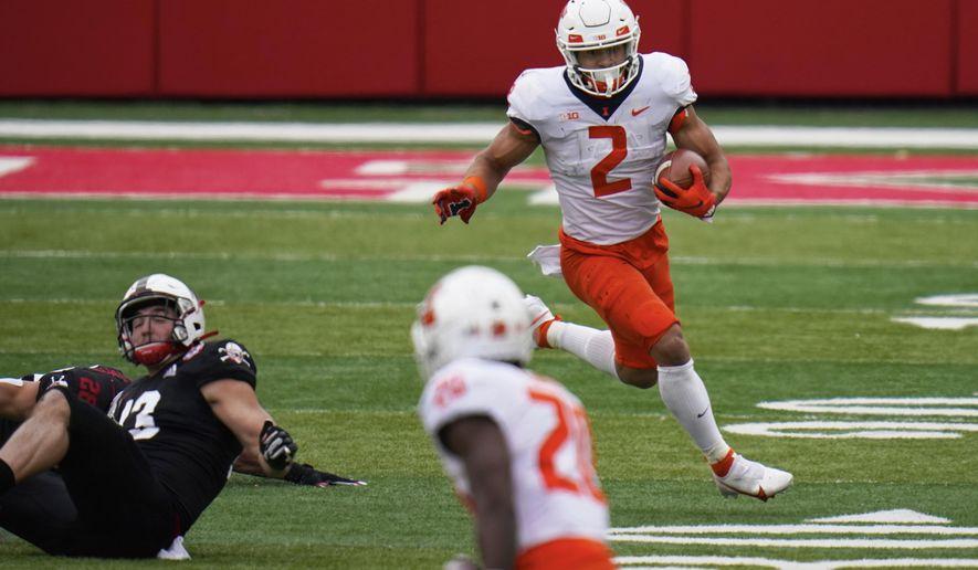 Illinois running back Chase Brown (2) runs past Nebraska linebacker JoJo Domann (13) during the first half of an NCAA college football game in Lincoln, Neb., Saturday, Nov. 21, 2020. (AP Photo/Nati Harnik)