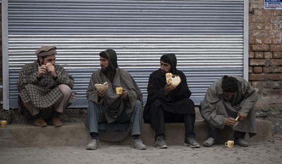 Kashmiri men drink tea on a cold day at a local market in Srinagar, Indian controlled Kashmir, Friday, Nov. 20, 2020. (AP Photo/Mukhtar Khan)