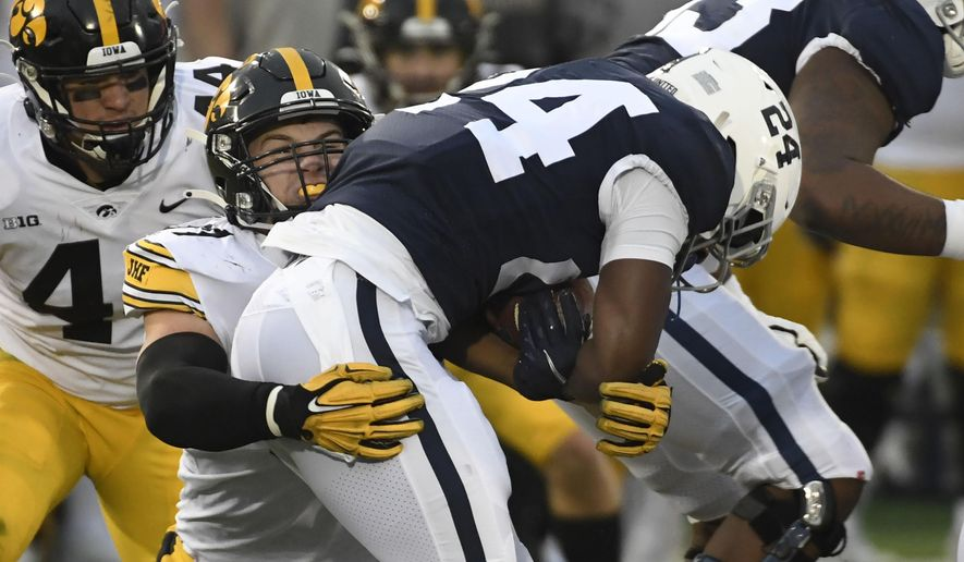 Iowa defensive lineman Zach VanValkenburg (97) tackles Penn State running back Keyvone Lee (24) during the first quarter of an NCAA college football game in State College, Pa., on Saturday, Nov. 21, 2020. (AP Photo/Barry Reeger)