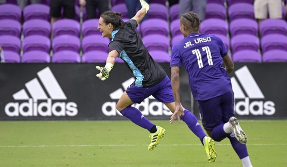 Orlando City defender Rodrigo Schlegel, left, celebrates after blocking the final New York City FC penalty kick during overtime of an MLS soccer playoff match, Saturday, Nov. 21, 2020, in Orlando, Fla. Schlegel was sent in to substitute for goalkeeper Pedro Gallese who was ejected after getting his second yellow card. (AP Photo/Phelan M. Ebenhack)