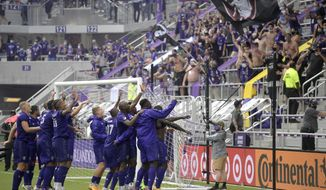 Orlando City players celebrate in front of fans after defeating New York City FC on penalty kicks in an MLS soccer playoff match, Saturday, Nov. 21, 2020, in Orlando, Fla. (AP Photo/Phelan M. Ebenhack)