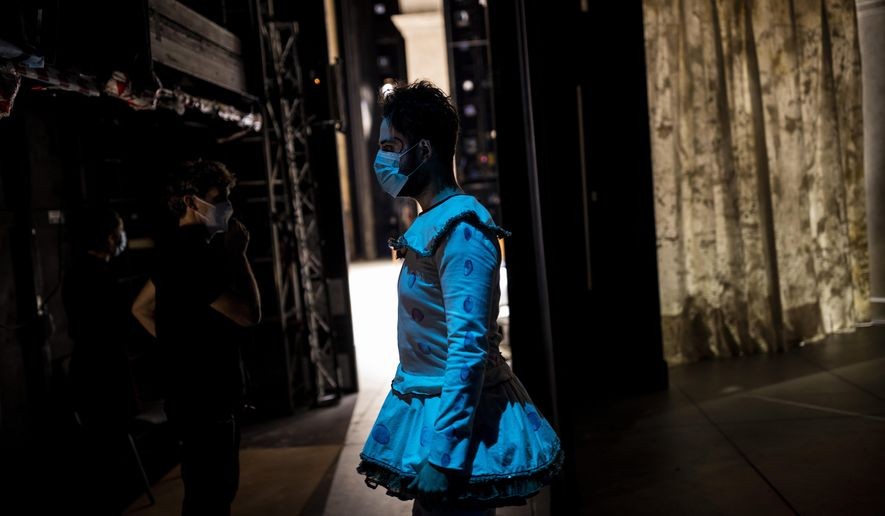 """Baritone Sebastia Peris, wearing a face mask, waits backstage during a performance of the opera """"Rusalka"""" at the Teatro Real in Madrid, Spain, on Thursday, Nov. 12, 2020. The theater is one of the few major opera houses that have reopened during the coronavirus pandemic, although to smaller audiences. (AP Photo/Bernat Armangue)"""
