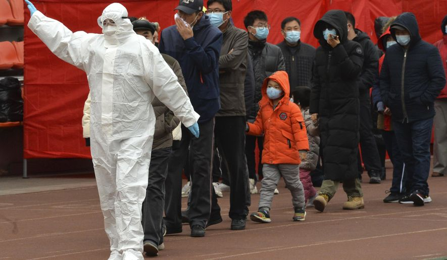 A worker wearing a protective suit gestures to a line of people at a COVID-19 testing site in Tianjin, China, Saturday, Nov. 21, 2020. China is starting mass testing on 3 million people in a section of the northern city of Tianjin and has tested several thousand others in a hospital in Shanghai after the discovery of a pair of cases there. (Chinatopix via AP)