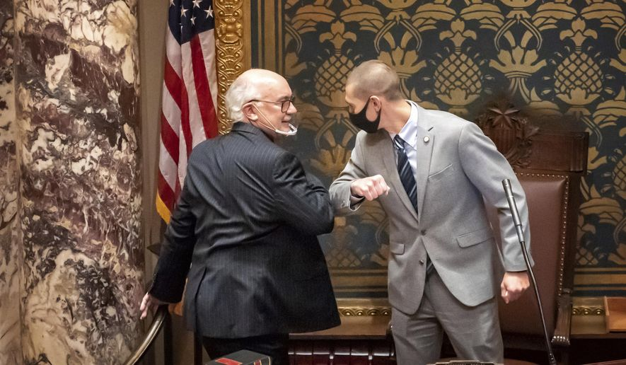 FILE - In this Nov. 12, 2020 file photo, outgoing Senate President Senate President Jeremy Miller, R-Winona gave Sen. David Tomassoni, DFL-Chisholm a congratulatory elbow bump before Tomassoni addressed the Senate Chamber. At least 187 state legislators nationwide have tested positive for the virus and four have died since the pandemic began, according to figures compiled by The Associated Press. Twelve Arkansas lawmakers have tested positive for the virus over the past month, the second largest known outbreak in a state legislature. (Glen Stubbe/Star Tribune via AP)