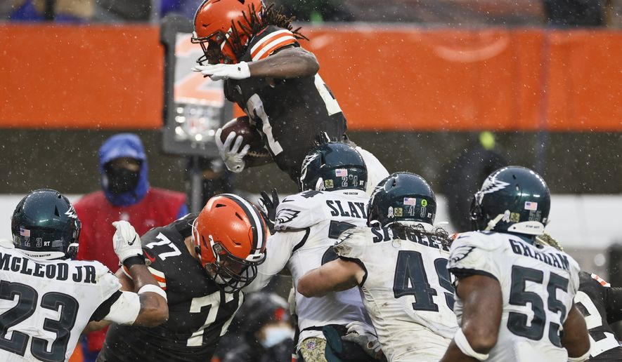 Cleveland Browns running back Kareem Hunt, top, rushes for a 5-yard touchdown during the second half of an NFL football game against the Philadelphia Eagles, Sunday, Nov. 22, 2020, in Cleveland. (AP Photo/Ron Schwane)