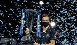 Daniil Medvedev of Russia holds up the winners trophy as confetti falls after defeating Dominic Thiem of Austria in the final of the ATP World Finals tennis match at the ATP World Finals tennis tournament at the O2 arena in London, Sunday, Nov. 22, 2020. (AP Photo/Frank Augstein)
