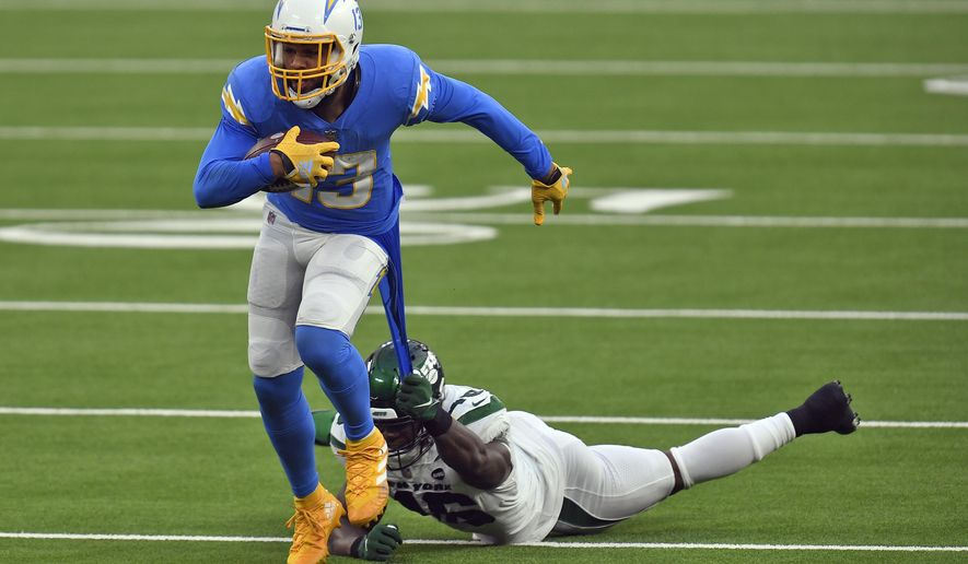 New York Jets linebacker Neville Hewitt, bottom, pulls on the jersey of Los Angeles Chargers wide receiver Keenan Allen after a catch by Allen during the second half of an NFL football game Sunday, Nov. 22, 2020, in Inglewood, Calif. (AP Photo/Kyusung Gong)