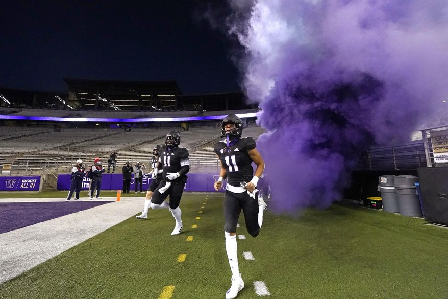 Washington players run from a purple cloud onto the field before an NCAA college football game against Arizona, in a stadium empty of spectators Saturday, Nov. 21, 2020, in Seattle. (AP Photo/Elaine Thompson)