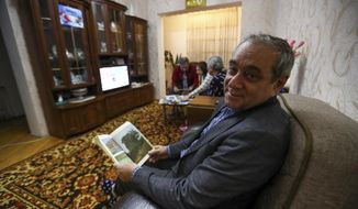 Adil Sharifov poses for a photo at home in Baku, Azerbaijan, Friday, Nov. 20, 2020. Adil Sharifov, 62, who left his hometown in 1992 during the first war and lives in Azerbaijan's capital, Baku, knows he will find similar devastation if he returns to the city of Jabrayil, which he longs to do. (AP Photo/Aziz Karimov)
