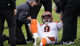 Cincinnati Bengals quarterback Joe Burrow (9) is helped getting off the field during the second half of an NFL football game against the Washington Football Team, Sunday, Nov. 22, 2020, in Landover. Bengals rookie suffered a left knee injury during this play and was carted off the field. (AP Photo/Susan Walsh)