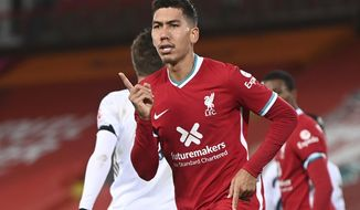 Liverpool's Roberto Firmino celebrates after scoring their sides third goal during the English Premier League soccer match between Liverpool and Leicester City at Anfield stadium in Liverpool, England. Saturday, Nov. 22, 2020. (Laurence Griffiths/Pool via AP)