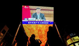 People wearing face masks to help curb the spread of the coronavirus gather near a giant TV screen broadcasting news of Chinese President Xi Jinping speaks as he participates in a virtual G-20 summit, at a shopping mall in Beijing, Sunday, Nov. 22, 2020. (AP Photo/Andy Wong) ** FILE **