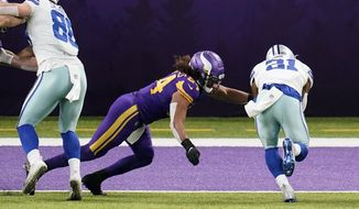 Dallas Cowboys running back Ezekiel Elliott (21) scores on a 6-yard touchdown reception ahead of Minnesota Vikings linebacker Eric Kendricks (54) during the first half of an NFL football game, Sunday, Nov. 22, 2020, in Minneapolis. (AP Photo/Jim Mone)