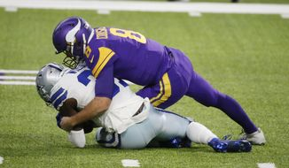 Dallas Cowboys safety Donovan Wilson recovers a fumble by Minnesota Vikings quarterback Kirk Cousins, right, during the first half of an NFL football game, Sunday, Nov. 22, 2020, in Minneapolis. (AP Photo/Bruce Kluckhohn)