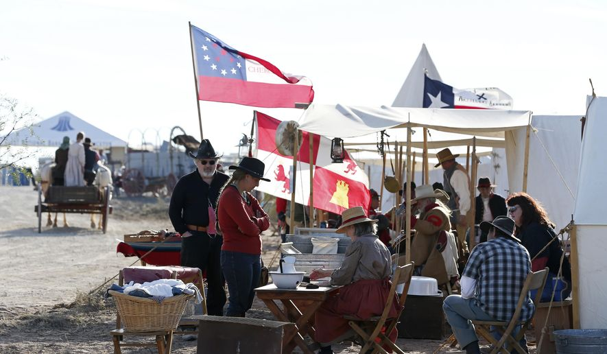 Several living history groups set tents up at Horse Head Crossing, a ford across the Pecos River, in Pecos County, West Texas, Oct. 30, 2020. A gathering of a few hundred people joined in the two-day celebration of the crossing. Comanche war parties returning from Mexico with stolen horses crossed here, as did immigrants and adventurers drawn by the California goldfields, as well as pioneering cattle drovers, including Charles Goodnight and Oliver Loving, pushing their leggy longhorns through to northern markets. (Jerry Lara/The San Antonio Express-News via AP)