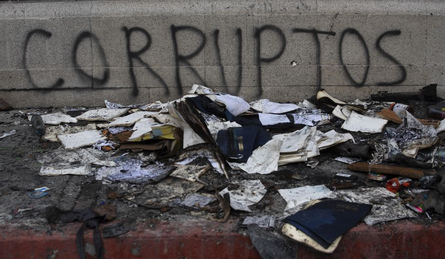 "Debris lays in front of graffiti that reads in Spanish ""Corrupt,"" outside of the Congress building that was damaged during protests in Guatemala City, Sunday, Nov. 22, 2020. Protesters broke into the building and set it partially on fire amid growing demonstrations against President Alejandro Giammattei and the legislature for approving a controversial budget that cut educational and health spending. (AP Photo/Moises Castillo)"
