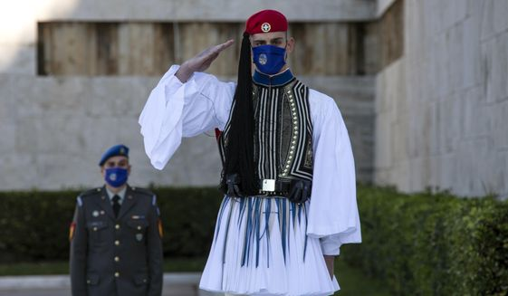 A Greek Presidential Guard, wearing a protective mask against the spread of coronavirus, salutes during a wreath laying ceremony, in Athens, Saturday, Nov. 21, 2020. The government imposed a second lockdown nationwide on Nov. 7, expanding regional restrictions, following a dramatic surge in COVID-19 cases. (AP Photo/Yorgos Karahalis)