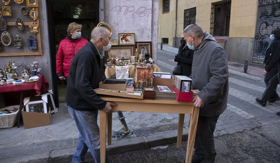 Stall-holders set up a table with antiques in the Rastro flea market in Madrid, Spain, Sunday, Nov. 22, 2020. Madrid's ancient and emblematic Rastro flea market reopened Sunday after a contentious eight-month closure because of the COVID-19 pandemic that has walloped the Spanish capital. (AP Photo/Paul White)