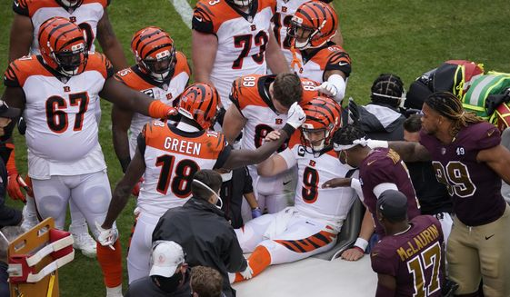 Cincinnati Bengals quarterback Joe Burrow (9) is consoled by teammate tight end Drew Sample (89) and other players before being moved off the field after injuring his left knee following a play in the second half of an NFL football game against the Washington Football Team, Sunday, Nov. 22, 2020, in Landover, Md. (AP Photo/Al Drago) **FILE**