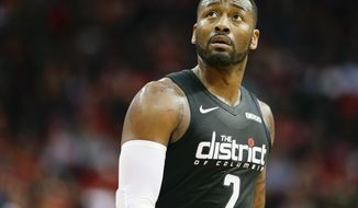 FILE - In this Dec. 19, 2018 file photo, Washington Wizards guard John Wall walks off the court during a timeout during the second half of an NBA basketball game against the Houston Rockets in Houston.  The Wizards general manager Tommy Sheppard says on Monday, Nov. 23, 2020, he has no plans to trade John Wall and is looking forward to seeing the point guard reunited in the backcourt with Bradley Beal.(AP Photo/Eric Christian Smith, File)