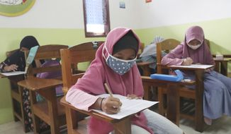 Students wearing face masks sit spaced apart during a trial run of a class with COVID-19 protocol at the  Nurul Amal Islamic school in Tangerang, Indonesia, Monday, Nov. 23, 2020. (AP Photo/Tatan Syuflana)