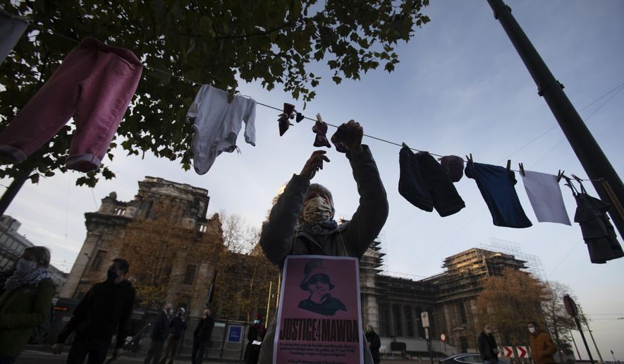 A woman hangs a piece of children's clothing on a line during a solidarity event for Mawda Shawri at the courthouse in Brussels, Monday, Nov. 23, 2020. A trial opened on Monday in the shooting death of two-year old toddler, Mawda Shawri, who was in a van during a high-speed chase between police and suspected migrant smugglers seeking to get to Britain. At the trial in Belgium's southern Mons, a policeman stands accused of involuntary manslaughter and two other men for being suspected migrant smugglers. (AP Photo/Virginia Mayo)