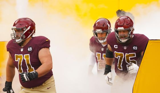 Members of the Washington Football Team taking the field, from l-r., offensive guard Wes Schweitzer (71), quarterback Alex Smith (11) and offensive guard Brandon Scherff (75) before the start of the first half of an NFL football game, Sunday, Nov. 22, 2020, in Landover. (AP Photo/Andrew Harnik) **FILE**