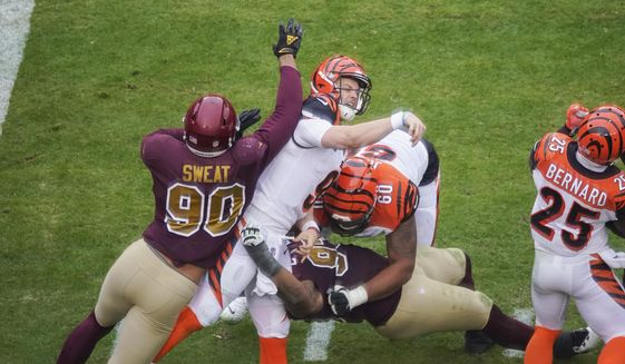 Cincinnati Bengals quarterback Joe Burrow (9) is hit and sandwiched inbetween Washington Football Team defensive end Montez Sweat (90), defensive tackle Jonathan Allen (93) and Cincinnati Bengals offensive guard Mike Jordan (60), during the second half of an NFL football game, Sunday, Nov. 22, 2020, in Landover, Md. After throwing a pass, Burrows was injured on this play and was carted off the field. (AP Photo/Al Drago)  **FILE**