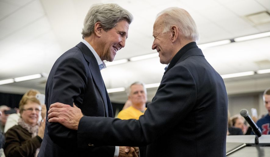 In this Feb. 1, 2020, file photo Democratic presidential candidate former Vice President Joe Biden smiles as former Secretary of State John Kerry, left, takes the podium to speak at a campaign stop at the South Slope Community Center in North Liberty, Iowa. (AP Photo/Andrew Harnik, File)