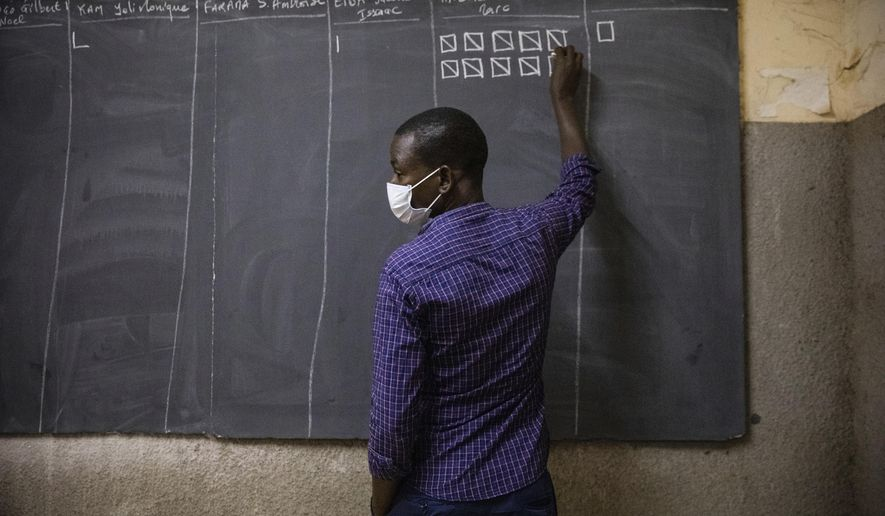 An election official counts the ballots in at a polling station in Ouagadougou, Burkina Faso, for the presidential and legislative elections late Sunday Nov. 22, 2020. (AP Photo/Sophie Garcia)