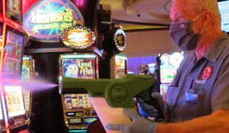 In this July 1, 2020 photo, Steven Ford, a worker at Harrah's casino in Atlantic City, N.J., sprays slot machines with disinfectant as the casino prepared to reopen after 3 1/2 months of being shut down due to the coronavirus. On Nov. 23, 2020, New Jersey gambling regulators released figures showing Atlantic City's casinos saw their gross operating profits decline by 37% in the third quarter of 2020 as they reopened under restrictions designed to slow the spread of the virus. (AP Photo/Wayne Parry)