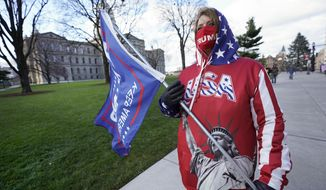 Lisa McClain, a President Trump supporter, walks near the Capitol building in Lansing, Mich., Monday, Nov. 23, 2020. Michigan's elections board is meeting to certify the state's presidential election results. (AP Photo/Paul Sancya)