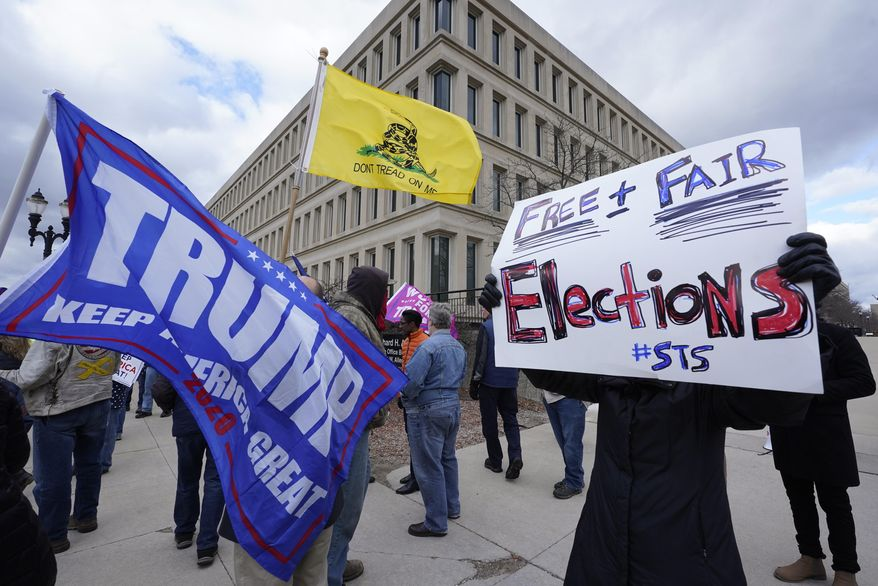 Protesters stand outside the Richard H. Austin state office building during a rally in Lansing, Mich., Saturday, Nov. 14, 2020. Michigan's elections board is meeting to certify the state's presidential election results. (AP Photo/Paul Sancya) **FILE**