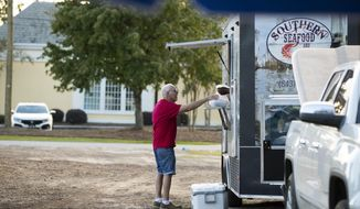 John King gets food to go from Southern Seafood and Catering's food truck at Yeamans Hall Canteen in Hanahan, S.C., on Friday, Oct. 23, 2020. The Hanahan resident says he comes to the food truck park for food several times per week. (Lauren Petracca/The Post And Courier via AP)