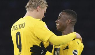 Dortmund's Erling Haaland, left, and Youssoufa Moukoko hug each other after the end of the game a German Bundesliga soccer match between Hertha BSC Berlin and Borussia Dortmund in Berlin, Geremany, Saturday, Nov.21, 2020. (Soeren Stache/dpa via AP)